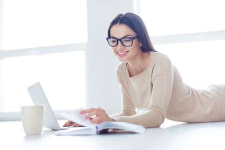 Het leuke slimme meisje in glazen ligt op de witte vloer en draait de pagina's om het dagboek, laptop en de kop zijn naast haar
