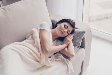 Portrait of a young cute brunette girl sleeping on the sofa in light livingroom. Her head is on grey pillow and she is covered with beige blanket