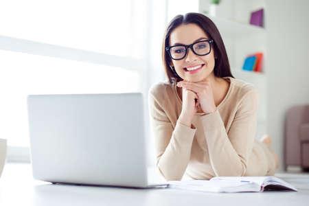 Portrait der netten nett-aussehenden lächelnden Geschäftsfrau in den Gläsern, die am Tisch mit Laptop, Notizblock auf ihm sitzen und ihren Kopf mit den Händen halten