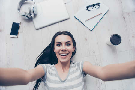 Wow! Amazed young cute girl is making selfie on the floor. She is having fun at home alone Stock Photo