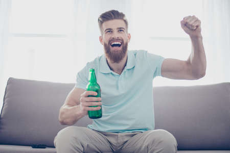 Cheerful young man is happy because of the goal of his favourite team. He is watching game at home with alcohol, sitting on sofa