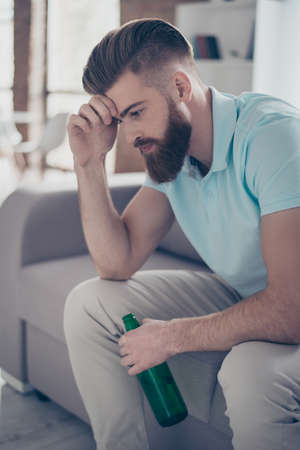 Frustrated young bearded man is holding his head, he is upset because his favourite team lost the game. He is having beer and sitting on the sofa at home