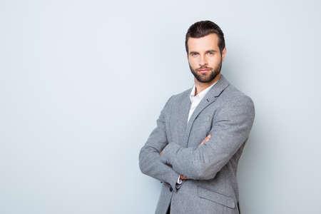 ハンサムの成功の肖像画を尊重の灰色の背景の交差させた手にフォーマルな服立っているビジネスマン