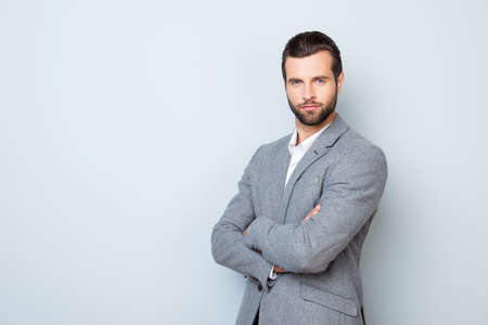 koncentrovaný: Portrét pohledný úspěšný respektovaný podnikatel ve formálním oblečení stojící se zkříženými rukama proti šedému pozadí