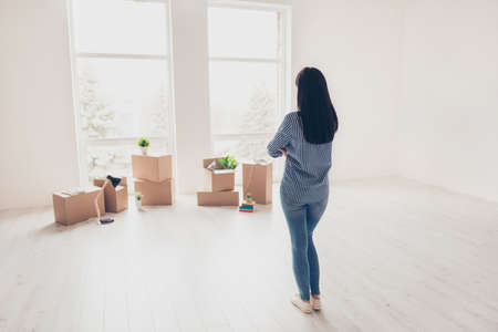 Dream come true! A start of new life! Brunette woman moved in to new light modern apartment and looking at boxes with her belongings, planning how she will organize the space here