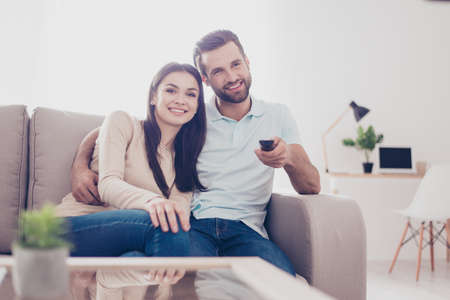 幸せなカップルは、抱いて家で映画を見ています。素敵なリビング ルームにはソファに座る。