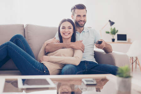 Cheerful couple is watching tv together and having fun. They are in the living room of their apartment Stock Photo