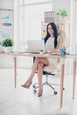 Successful stunning businesswoman is working at her nice modern office. She is wearing high hills, white elegant dress