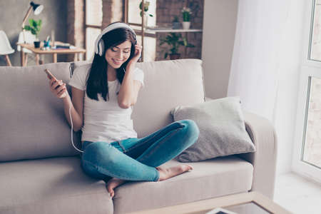 earbud: Excited beautiful brunette teen is listening to music in big white earphones at home. She is wearing casual clothes, sitting on comfortable sofa with crossed legs and closed eyes