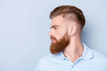 Side view close up portrait of handsome bearded young serious man in polo isolated on copyspace Imagens