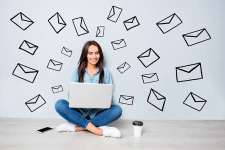 Concept of modern lifestyle. Young friendly  pretty happy student sitting on floor and typing on laptop mail, envelope icon draw Stock Photo