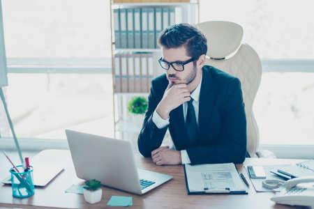 Nadenkende jonge slimme ondernemer in zwart pak en bril zorgvuldig lezen van de informatie in het interent