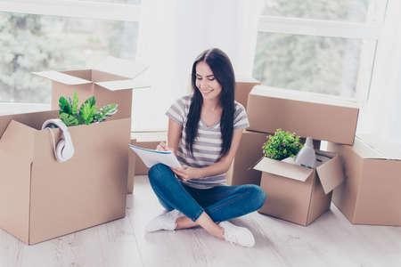 Trautes Heim, Glück allein! Nettes jugendlich in der zufälligen Kleidung sitzt mit den gekreuzten Beinen auf dem Boden ihrer neuen Wohnung. Eine Menge ausgepackter Kisten in ihrer Nähe