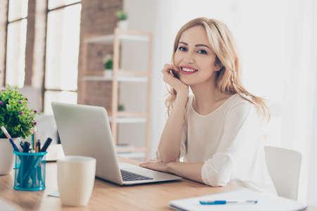 コンピューターと作業中のテーブルに座って幸せなかわいい女 写真素材
