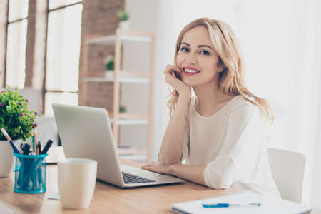 Happy pretty cute woman sitting at the table working with computer