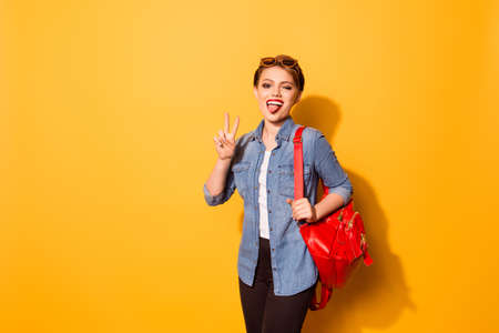 Playful young girl with red lipstick and tongue out in stylish sunglasses on the yellow background. She is excited, holding her bright red backpack