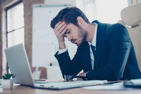 Jonge moe, ziek, overwerkte man in formele slijtage zit achter de computer en aanraken van zijn voorhoofd