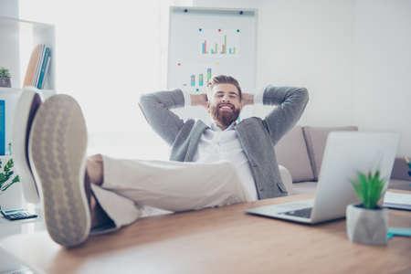 陽気な青年実業家は、机の上に足で、職場で休んでいる笑みを浮かべて