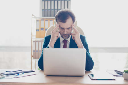 Close up portrait of serious focused businessman sitting at the desktop in office and work with laptop. He is concentrated with choosing the options of future projects