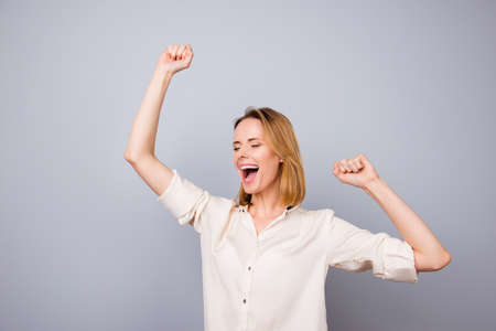 hooray: Happy woman laughing and triumphing with raised arms against gray background