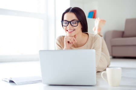 Cute smart girl with glasses lies on the floor, looks at the laptop screen and smiles