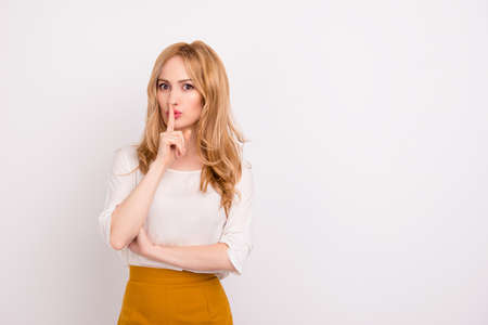Portrait of mysterious businesswoman gesturing shh! against white background