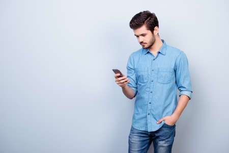 Vertical portrait of young guy in jeans shirt, typing sms and holding his hand in pocket on pure light background Фото со стока