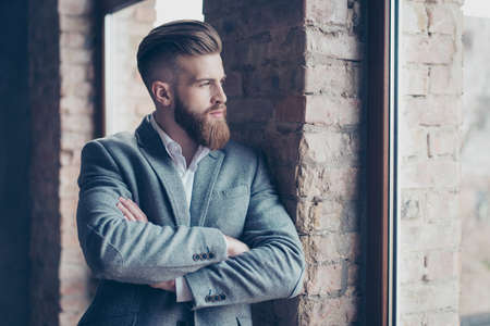 Close up portrait of handsome bearded young man in suit leaning on brick wall and looking out of the window