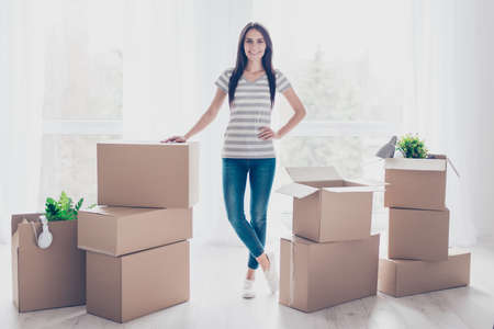 Young pretty lady is moving to new place. She is satisfied, she collected her belongings in boxes Фото со стока