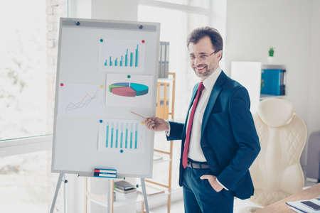 El hombre de negocios acertado sonriente está divulgando con el rotafolio en oficina. Viste traje azul, lentes y corbata roja.