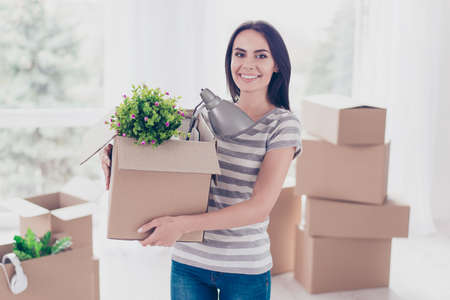 Cheerful young pretty brunette is packing her stuff at the box to move to new place. She is happy and can`t wait Foto de archivo