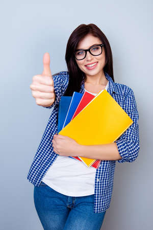 Smart female student in glasses and checkered shirt holding books and showing like gesture against gray background Zdjęcie Seryjne - 80830976