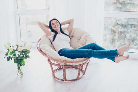 Cheerful young cute pretty woman enjoying  weekend while sitting on comfort soft modern armchair with white rose at home