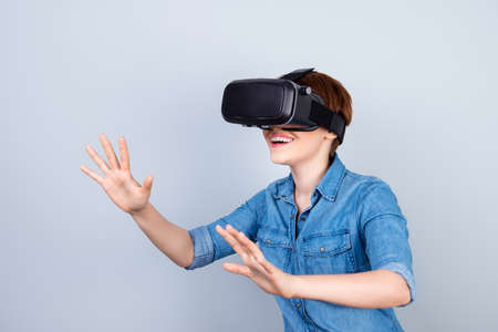 Happy young girl is using vh headset glasses of virtual reality, touching something with her hands like a touch screen 스톡 콘텐츠