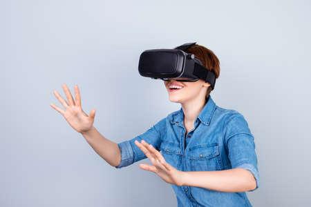 La ragazza felice sta usando i vetri della cuffia avricolare della realtà virtuale, toccando qualcosa con le sue mani come un touch screen Archivio Fotografico - 80830970