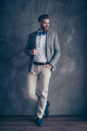 Foto in voller Länge des überzeugten stilvollen Mannes mit rotem Bart und blauer Fliege mit der Hand in der Tasche Standard-Bild