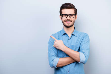 Cheerful handsome young man i glasses is showing direction and pointing with his finger Archivio Fotografico