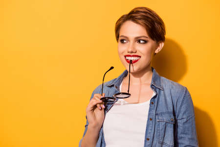 Close up portrait of a playful young stylish girl. She is in a jeans shirt and has a bright red lips, standing on the yellow background, holding spectacles