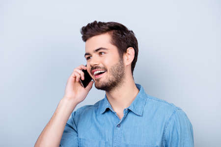 Excited young handsome boy is talking on his smartphone and smiling. He is wearing jeans shirt and behind him is a pure blue background