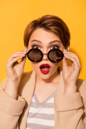 Omg! Close up portrait of amazed girl with red pomade in stylish sunglasses and casual wear on the bright yellow background Stock Photo