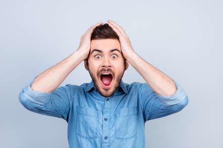 Oh mio Dio! Non c'è modo! Il giovane molto scioccato sta tenendo la sua testa con le mani bith. Indossa una camicia elegante di jeans Archivio Fotografico - 80832509