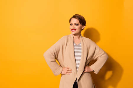Stylish young beautiful girl in fashionable  beige cardigan is standing on bright yellow background. She looks excited and her smile is adorable Imagens