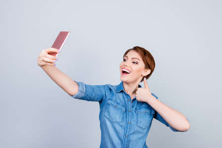 Young playful girl is making selfie on the camera of her telephone and showing like sign Stock Photo
