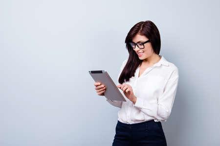 かなり若いワーカー女性フォーマルな服と眼鏡デジタル タブレットを保持していると、インターネット上でいくつかの情報を探しています。
