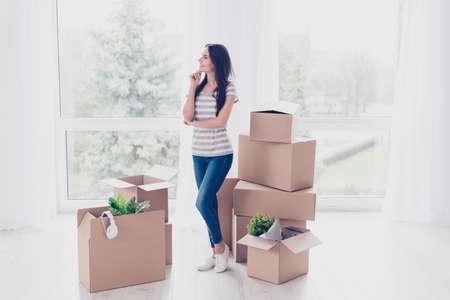 Verträumte Mädchen denkt, wie sie alles organisieren wird, wenn sie ihre neue Wohnung hat, die sie gerade hineingezogen hat Standard-Bild
