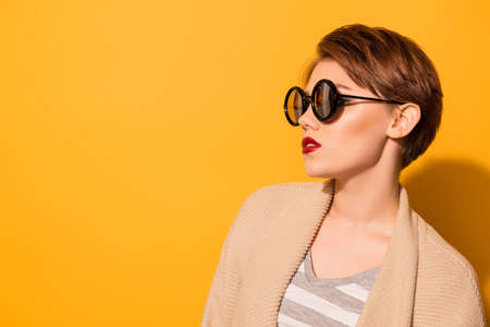 Fashionable look of the model in stylish sunglasses and casual clothes on the bright yellow background 스톡 콘텐츠