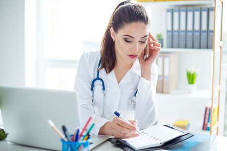 Photo of smart young confident female doctor sitting at the table receiving a call from a patient and writing information in notepad Stock Photo
