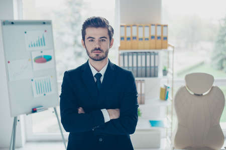 1 person: Concept of successful young confident businessman. Concentrated man with crossed arms standing in front of shelves full of folders and board with graphs Stock Photo