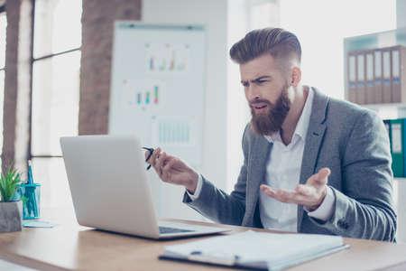 ショックを受けた若い実業家がメガネをはずしたし、ノート パソコンを見て、彼は受賞ニュースを信じることができません。