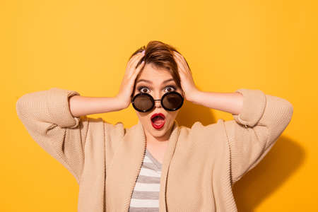 No way! Close up portrait of shocked girl in stylish sunglasses and casual wear on the yellow background